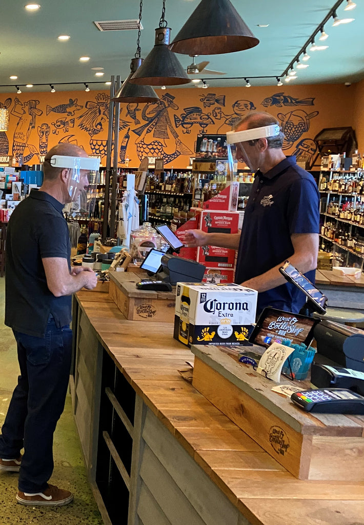 Male cashier and male customer interacting while wearing Hardwire Face Shields.