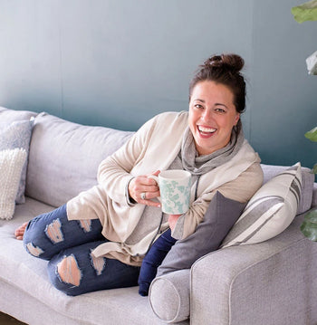 Kara-Hubbard-On-Couch-With-Coffee-Mug, business coach for photographers, business help, natural light photography, grey couch,