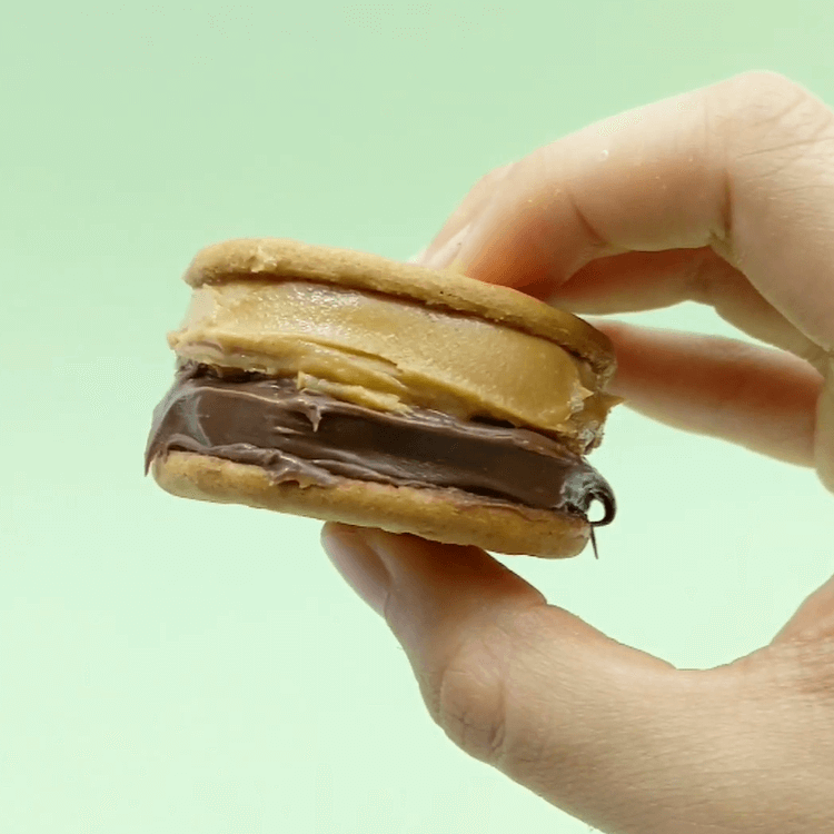 bts all night sandwich cookie with chocolate spread and peanut butter hand holding against green background