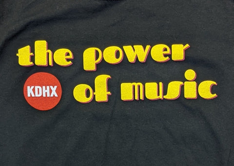 "A close up photograph of the design on the black t-shirt. ""The Power of Music"" is written in yellow, 70's-style retro bubble letters with a red double shadow underneath each letter and a black background. The sentence wraps around the red circular KDHX logo in the lower left corner."