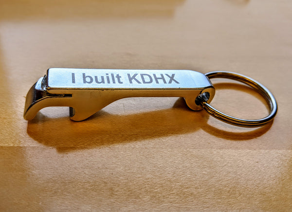 A small, metal bottle opener on a keychain engraved with the words I built KDHX
