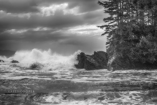 Black and white image of crashing waves on rocky ocean island.