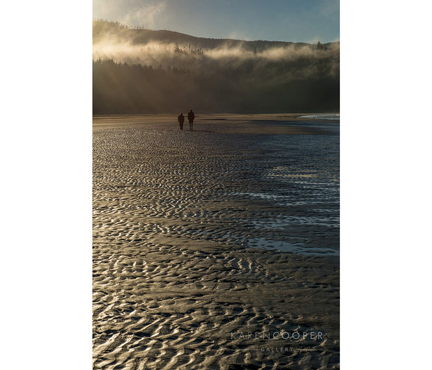A misty beach near sunset with two human figures walking away from the camera.