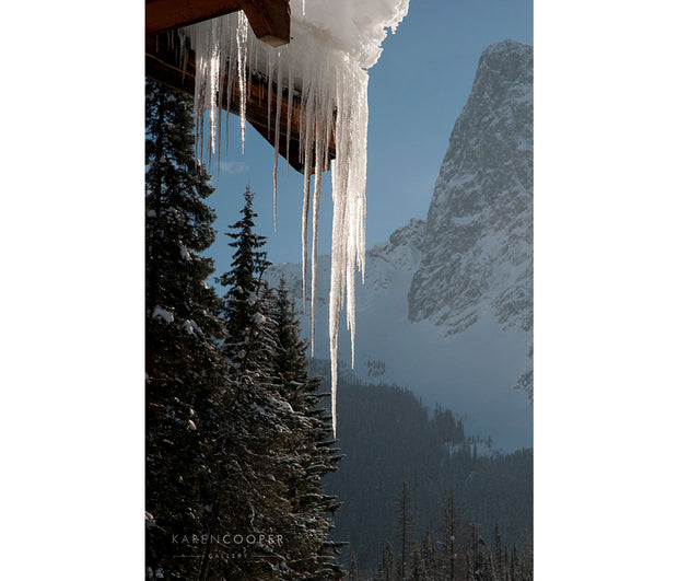 Detail of thick, clear icicles on the gable of a roof, overlooking a steep, snow-capped mountain and large, snow covered evergreen tees. The sun is shining on the ice.