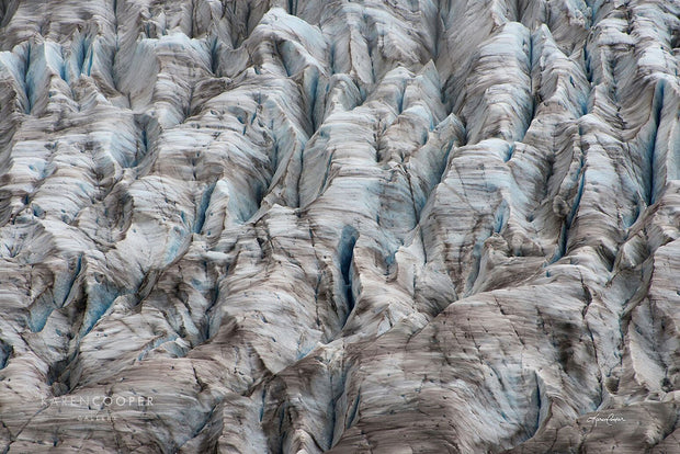 A rugged glacier, dotted with brown lines and deep cracks and crags.