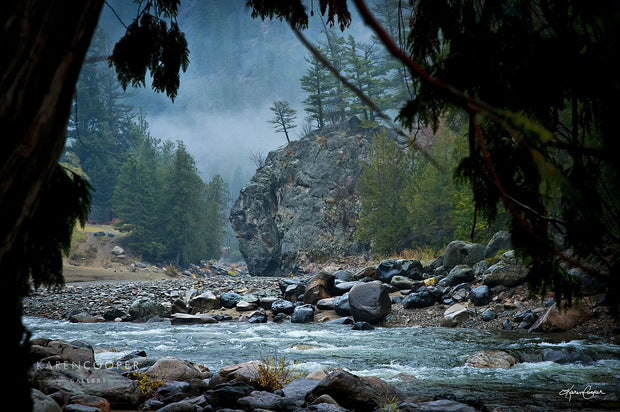 A large boulder jutting into the similkameen river, covered in smaller, blue, grey, and black stones on a misty day