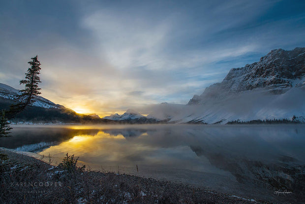 Fine art luxury nature landscape contemporary photography by Karen Cooper Gallery A large, still lake perfectly reflecting the blue, twilight sky and the remaining golden sun rays seen just over the snow-capped mountains. in the winter in a Alberta provincial park in Canada