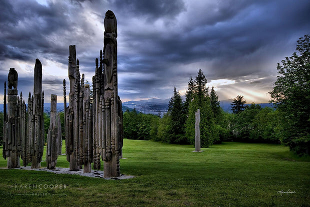 Various Ainu wooden sculptures in a green park on Burnaby Mountain, overlooking the storm-covered sky with sun rays jutting through a small hole onto the mountains and city in the background.