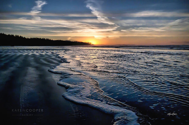 Tide coming into a soft, sandy beach at sunset, with streaks of cloud along a deep blue sky.