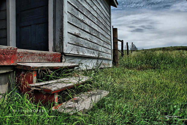 Detail of weathered stairs leading up to the porch of an old, abandoned farmhouse, surrounded by clouds, a barbed wire fence, and short green grasses