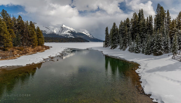 A clear, shallow river with their shores covered in white, pristine snow. Flanked by two sets of evergreen trees, and in the centre background a tall, jagged, snow covered mountain framed by thick white clouds with patches of blue sky.