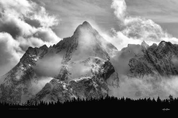 Black and white of one of the Seven Sisters mountain peak. Base of mountain dominated by the profile of evergreen trees. Rugged sharp peaks covered with rolling, thin clouds.