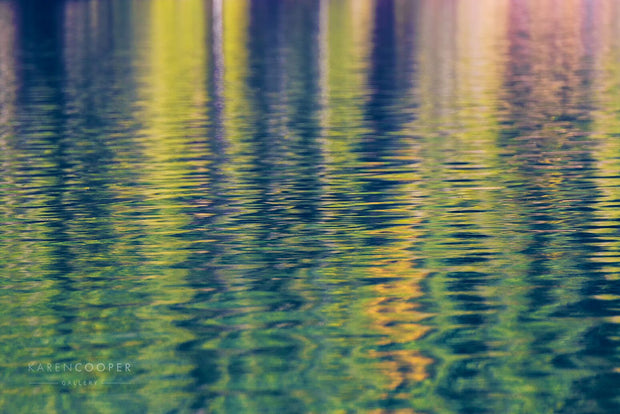 green trees reflected in rippling water