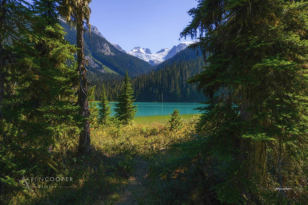 A turquoise, still lake surrounded by lush, green evergreens and tree and snow-capped mountains. A pathway is leading toward the lake near Whistler in British Columbia