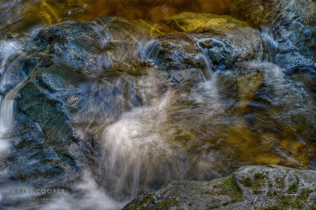 gold water flowing over dark rocks in a creek