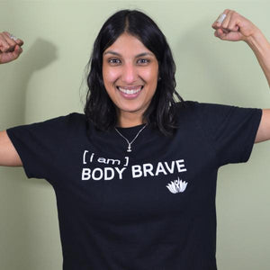 "Person smiling wearing black short sleeve t-shirt with the words, ""I am Body Brave"" written in white"