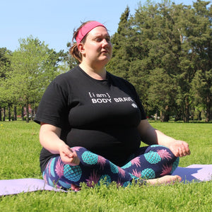 "Person outside in a grassy park sitting with their legs crossed and eyes closed on a yoga mat. They are wearing a black t-shirt that says, "" I am Body Brave"" on the front in white. There are trees behind them and the sky is blue."