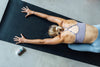 Woman in a Sports Bra stretching out on a yoga mat with a stick of natural deodorant