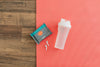 Protein Shaker, Ear Buds, and Deodorant Wipes on a Yoga Mat
