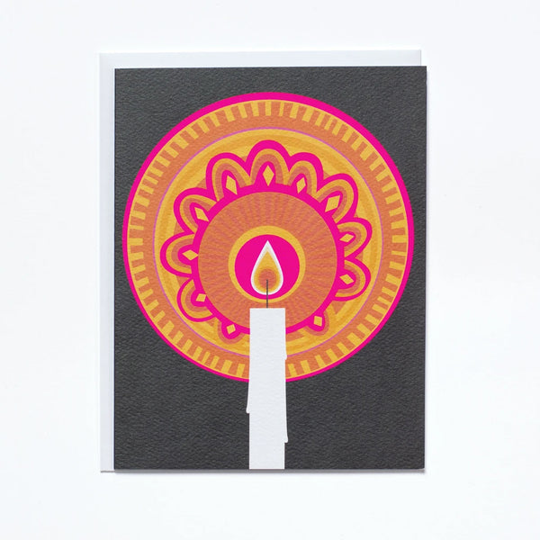 Greeting Card by Banquet with a glowing orb of pink and orange light surrounding a single flaming candle on a black background