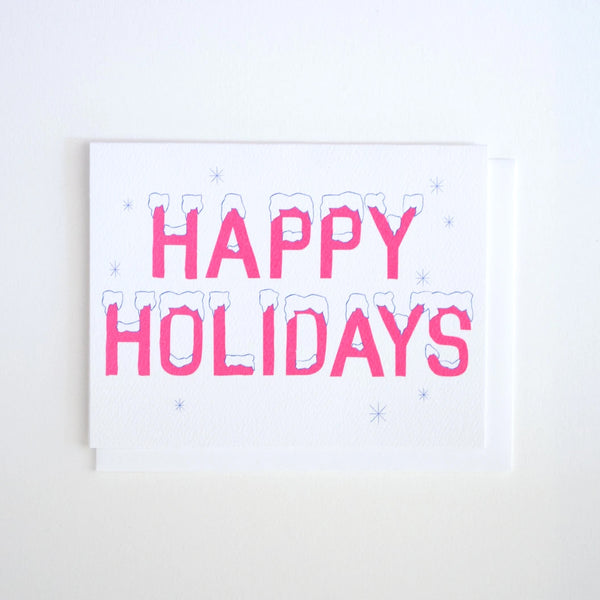 Greeting Card by Banquet with pink Happy Holidays lettering with snow on top on a white background