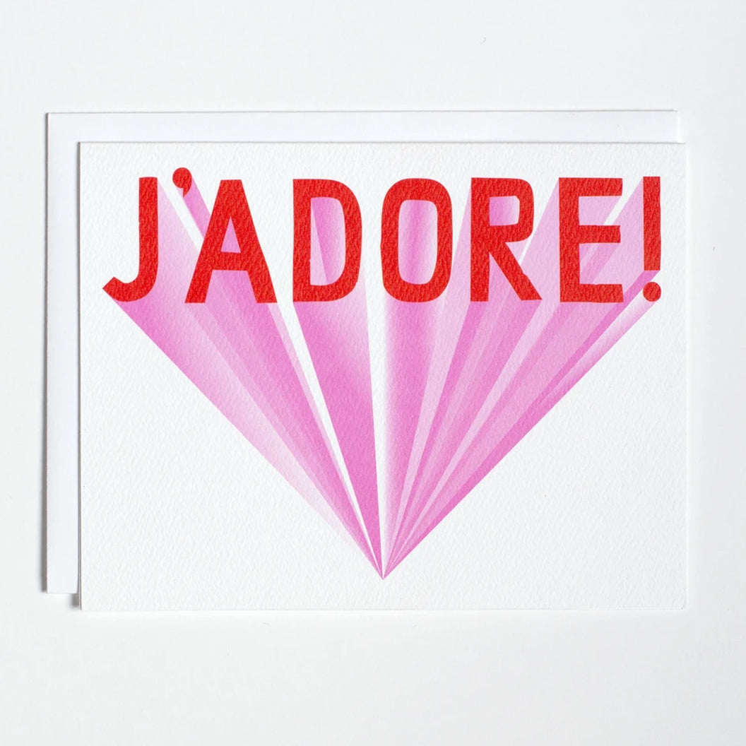 Greeting card with red lettering and pink backdrop that says J'Adore by Banquet Workshop