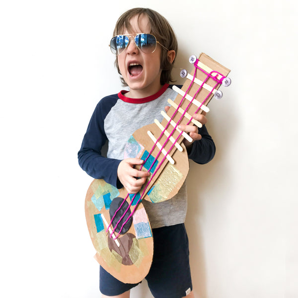 Boy with handmade guitar from virtual Art class inspired by Joni Mitchell