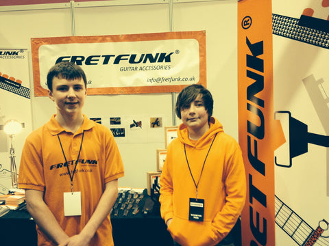 Kids work the stand at Birmingham guitar show apprentice style
