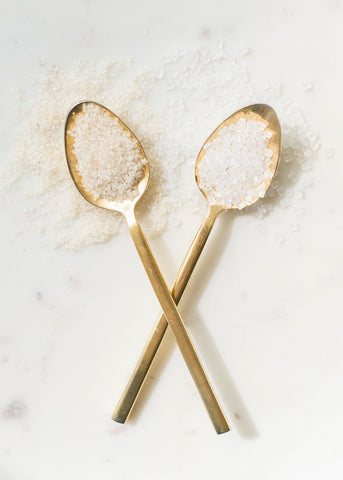 2 brass spoons crossed each filled with sugar
