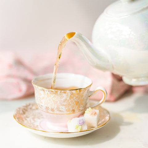 pearlescent teapot pouring tea into china tea cup