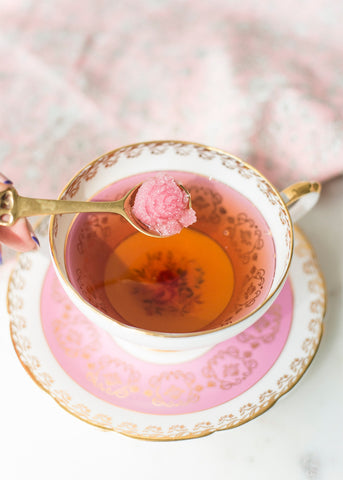 spoon holding sugar rose over china tea cup