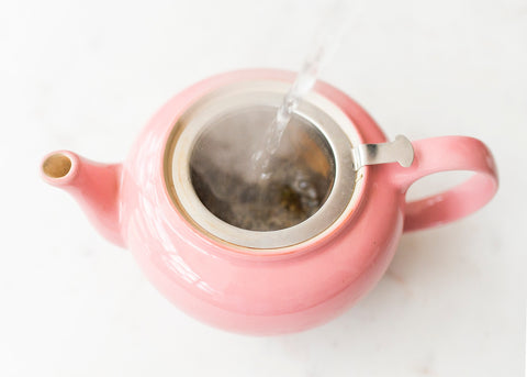 pink le creuset teapot filled with Sloane Tea
