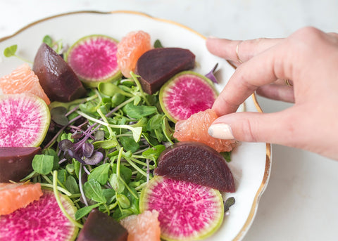 hand placing grapefruit and beets on salad