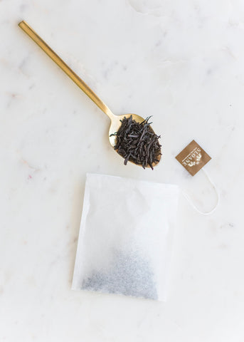 brass spoon filled with earl grey loose leaf tea