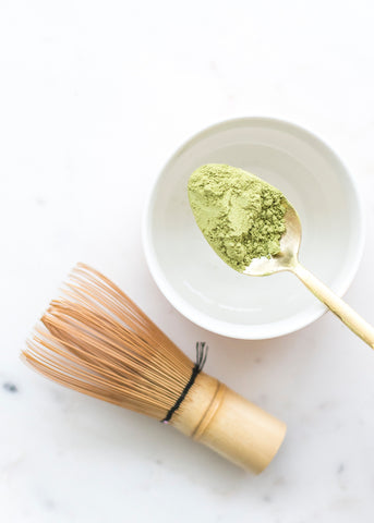 spoon holding organic matcha near whisk