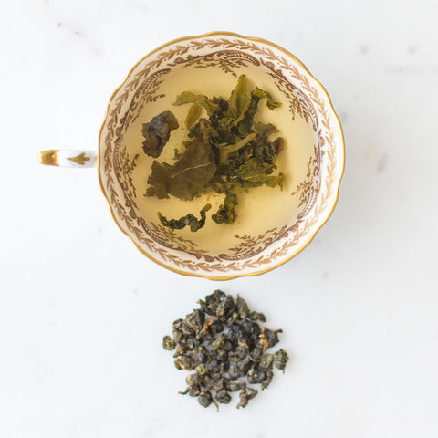 Oolong tea infused in cup with dried loose leaf beside