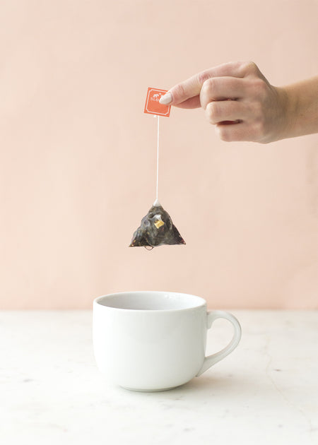 Pyramid sachet held over white mug