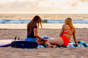 surfer girls sitting on beach sunset skateboard surfboard swimwear