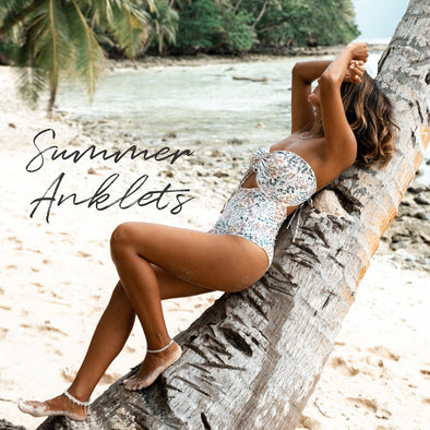 model wearing anklet jewellery, swimsuit while lounging on palm tree