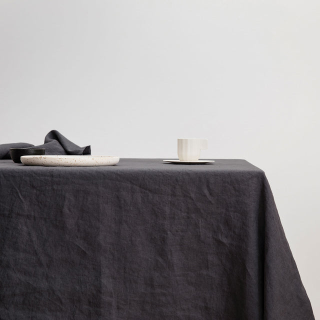 The Linen Tablecloth in Slate styled with a white ceramic plate and white cup and saucer.