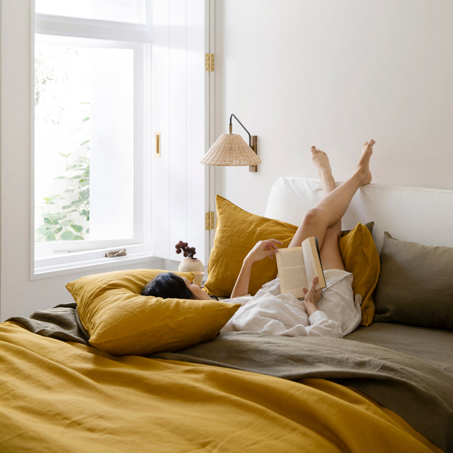 A bed styled with a Linen Duvet Cover Set in Mustard and Linen Flat Sheet with Border, Linen Fitted Sheet and Set of 2 Linen Pillowcases in Olive. A model is on top of the bed in a Claude Linen Shirt in Natural. She is lying down reading a book.