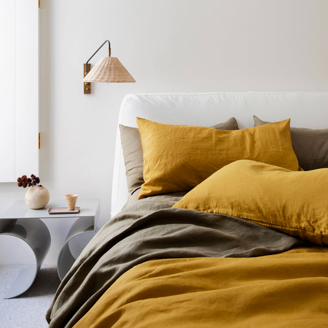 A bed styled with a Linen Duvet Cover Set in Mustard and Linen Sheet Set in Olive. To the left of the bed there is a grey side table with a small ceramic cup on a tray and a bunch of dark red flowers in a small round vase.