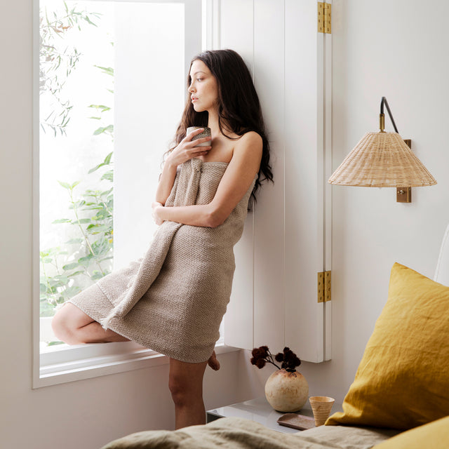 A model with fair skin and dark hair is leaning against a window whilst wrapped in the Pure Linen Bath Towel in Natural. Next to her is a bed styled with Mustard linen, and a sconce with a rattan shade.