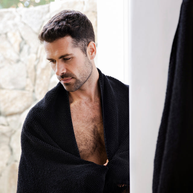 A male model with dark hair has a Pure Linen Bath Towel in Black wrapped around his shoulders