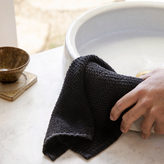 The Pure Linen Wash Cloth in Black draped over a white sink. There is a hand on the Wash Cloth.