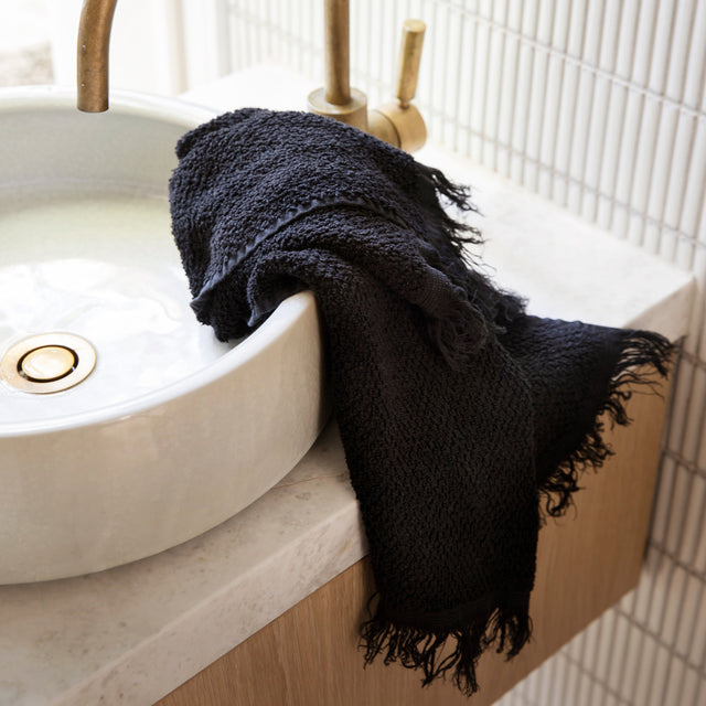 The Pure Linen Hand Towel  in Black draped over a white sink. The hand towel has visible black fringing.