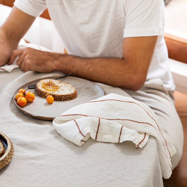 A man wearing a white shirt sitting next to a table that is styled with a Linen Tablecloth in Natural, Linen Table Napkin in Cedar Stripe and ceramic plate with a slice of bread with jam and tomatoes on top.
