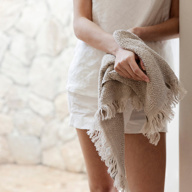 A model in beige linen shorts and a singlet is drying her hands with a Pure Linen Hand Towel in Natural.