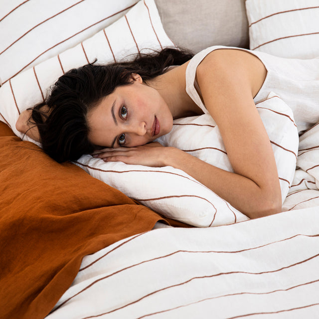 A model lying in a bed styled with a Linen Duvet Cover Set in Cedar Stripe and Linen Flat Sheet with Border in Cedar. The model has fair skin and dark hair.
