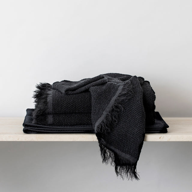 Stack of Pure Linen Towels and a Bath Mat in Black